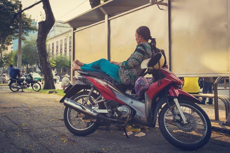Een niet geïdentificeerde vrouwenrust op haar motor in Vietnam stock foto's