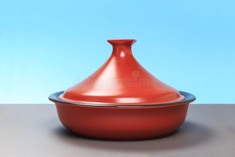 Een nieuwe ceramische pan bevindt zich op een grijze lijst en een blauwe achtergrond Close-up royalty-vrije stock foto's