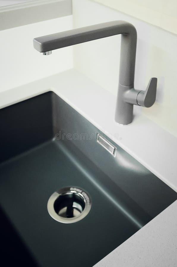 Een nieuwe zwarte die keukengootsteen van kunstmatige steen en een tapkraan wordt gemaakt Het concept modern keukenbinnenland Ver stock afbeelding