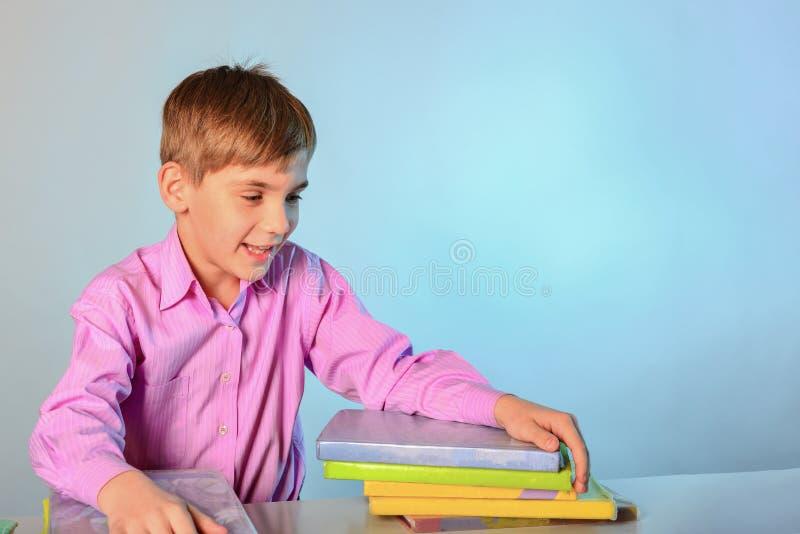Een nieuwsgierige tiener koestert boeken terwijl het zitten bij een bureau stock fotografie