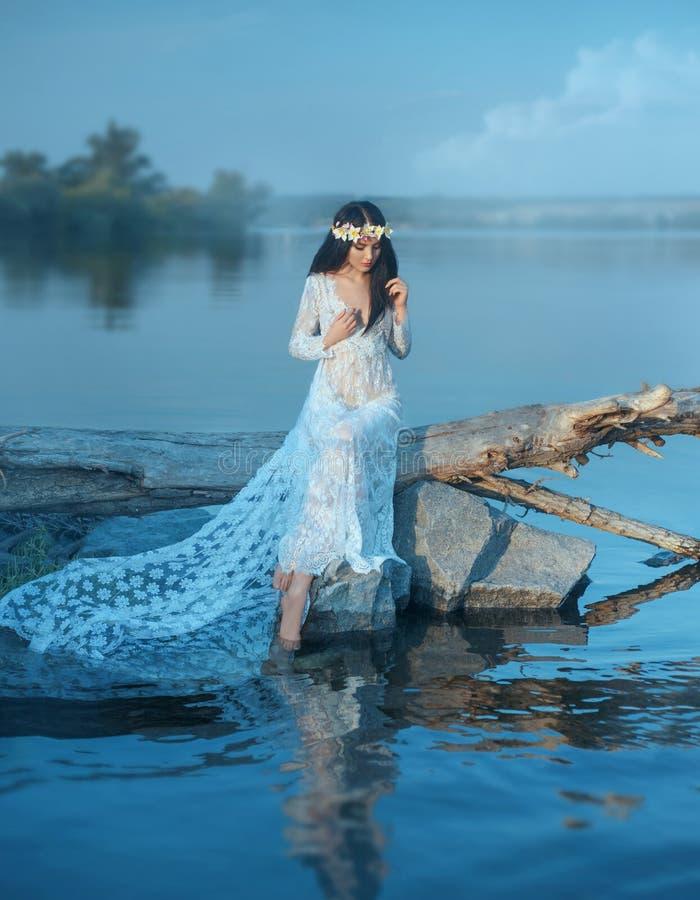 Een nimf met lang donker haar in een witte uitstekende kleding zit op een logboek over de rivier in het haar een kroon van lelies stock afbeelding