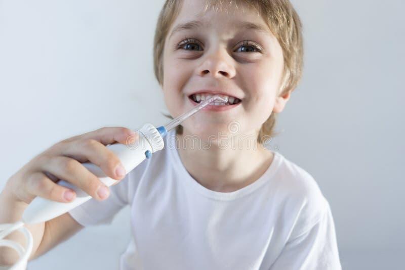 Een 5 ??njarigenjongen zit thuis bij een witte lijst in een witte t-shirt en wast zijn tanden met een mondelinge irrigator De jon stock foto