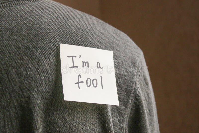 Een nota over de rug van een jonge mens met een grappige tekst Een grap door fir van April royalty-vrije stock afbeelding