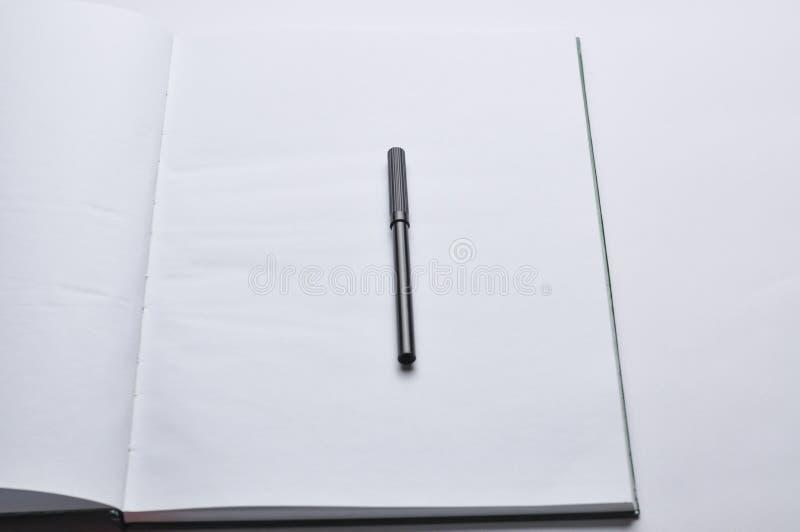 Een notitieboekje en een rode en zwarte pen op een witte achtergrond De ruimte van het exemplaar royalty-vrije stock afbeelding