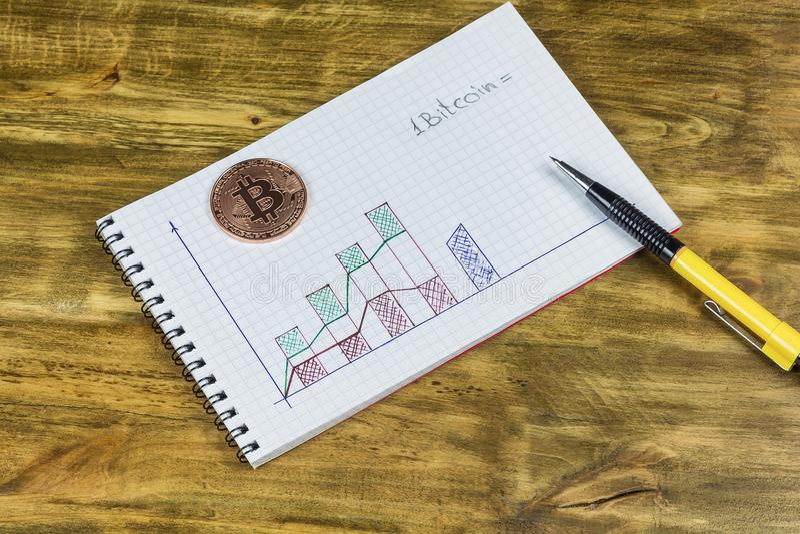 Een notitieboekje met een grafiek, een pen en een platinamuntstuk Bitcoin stock fotografie