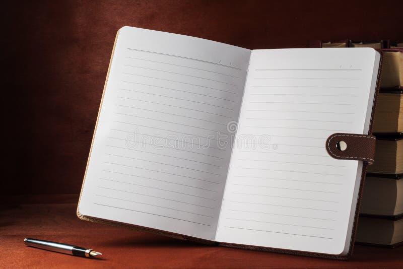 Een notitieboekje met handboeken op een houten lijst royalty-vrije stock afbeelding