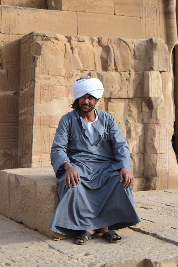 Een Nubian-mensenzitting in een tempel in Egypte, Aswan Luxor stock afbeeldingen