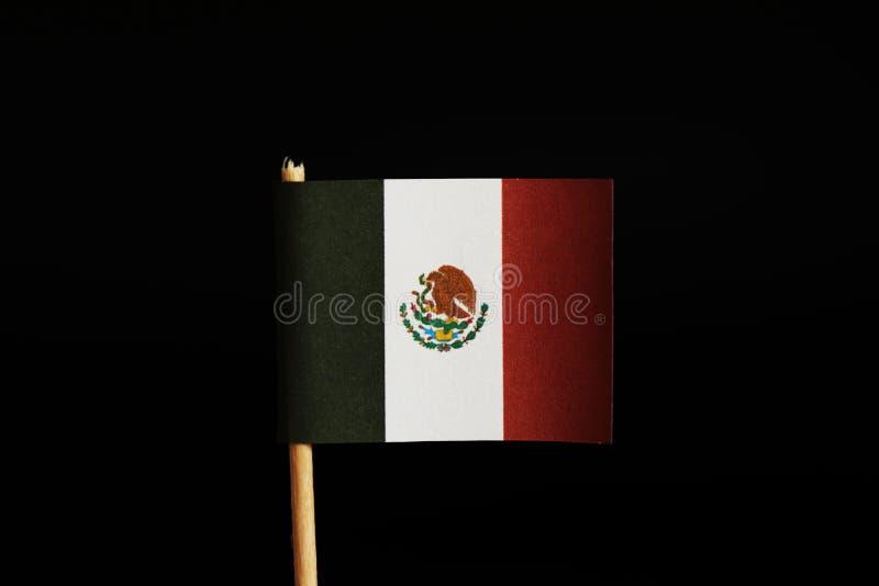 Een officiële vlag van Mexico op tandenstoker en op zwarte achtergrond Mexico behoort tussen het meeste misdadigheidsland in de w stock afbeelding