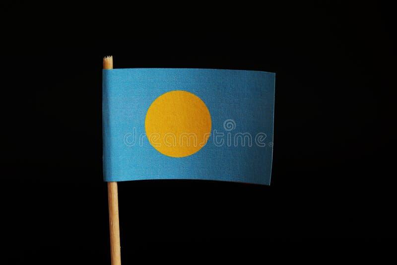 Een officiële Vlag van Palau op houten stok op zwarte achtergrond Palau behoort tot Oceanië Palau is eilandstaat stock afbeeldingen