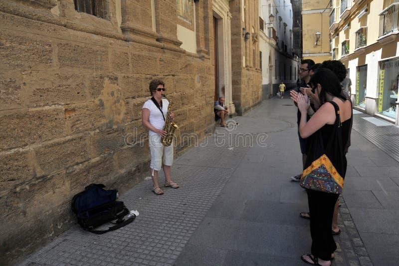Een onbekende vrouw speelt de saxofoon op de oude straat van de stad van Cadiz stock afbeeldingen