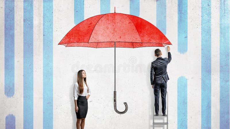 Een onderneemster bevindt zich dichtbij een muur waar een zakenman een reuze rode paraplu trekt die hen behandelen van de regen stock foto