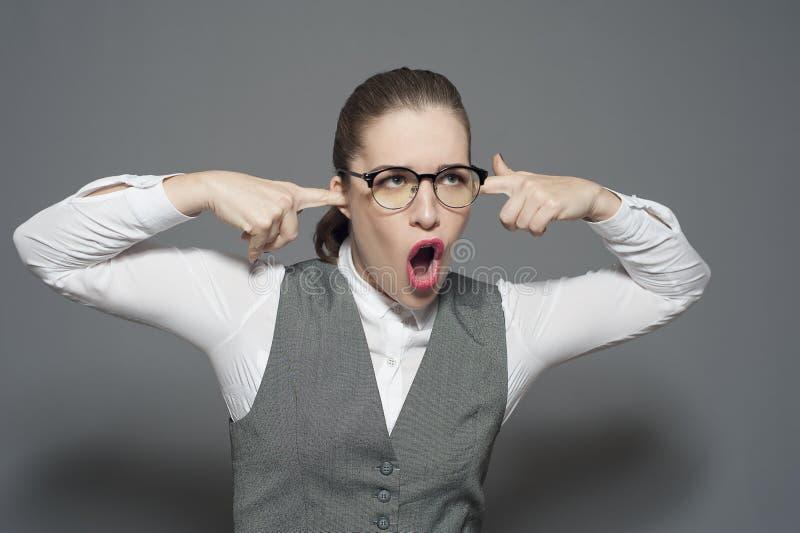 Een onderneemster sluit haar oren en schreeuwt royalty-vrije stock afbeelding