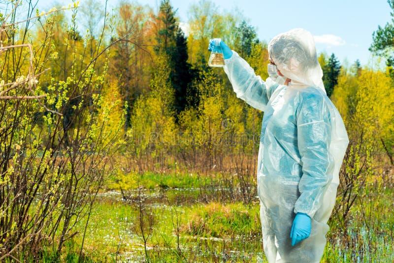een onderzoekers chemicus-milieudeskundige leidt een visuele inspectie van water royalty-vrije stock foto