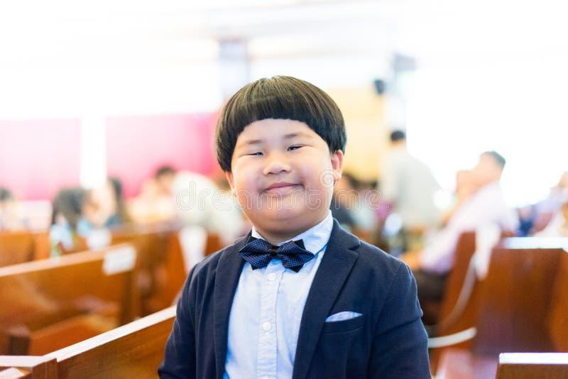 Een ongehoorzame jongen maakt grappig gezicht, speelt hij in de kerk stock fotografie