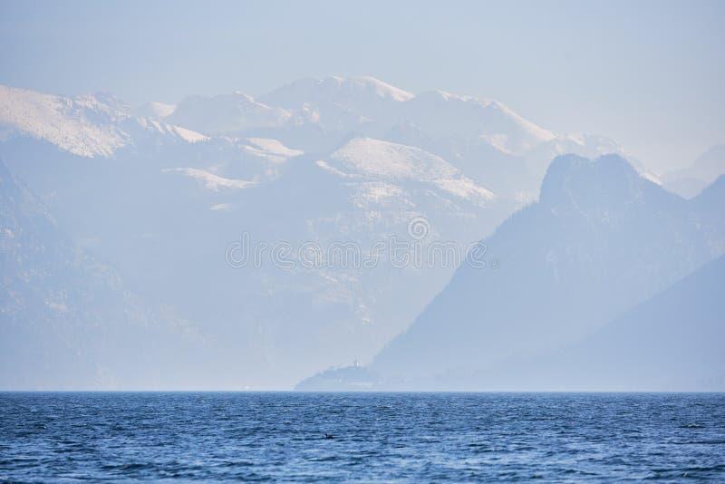 Een ongelooflijk landschap van het meer Traunsee in Oostenrijk Het blauwe meer daalt in de de herfstnevel stock afbeeldingen
