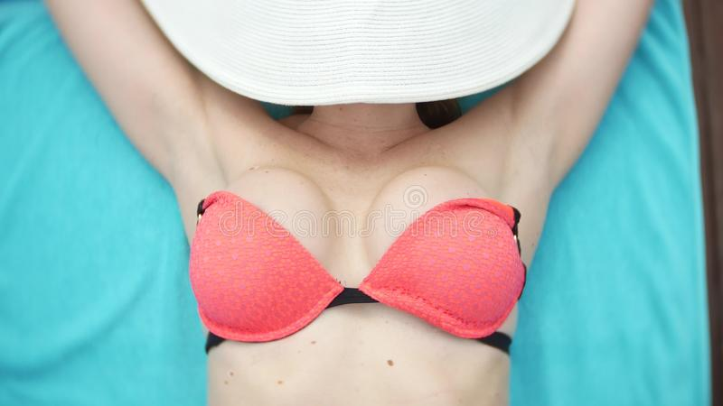Een onherkenbare slanke rondborstige vrouw in een grote witte hoed en een roze bikini ligt op een chaise zitkamer dichtbij de poo stock foto