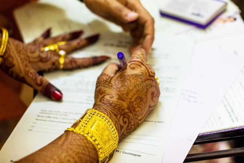 Een onlangs gehuwde Indische Bengaalse vrouw met gouden ornament en blacelet die de vorm van de huwelijksregistratie ondertekenen royalty-vrije stock afbeelding