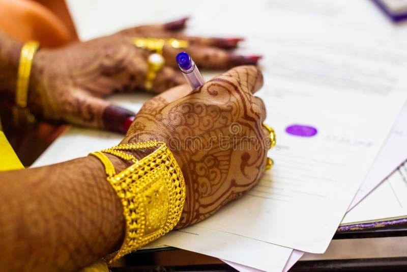Een onlangs gehuwde Indische Bengaalse vrouw met gouden ornament en blacelet die de vorm van de huwelijksregistratie ondertekenen royalty-vrije stock foto's