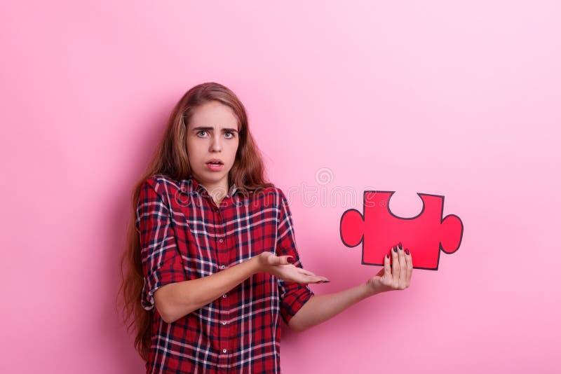Een ontevreden meisje, punten aan een groot raadsel dat zij in handen houdt Op een roze achtergrond stock afbeelding