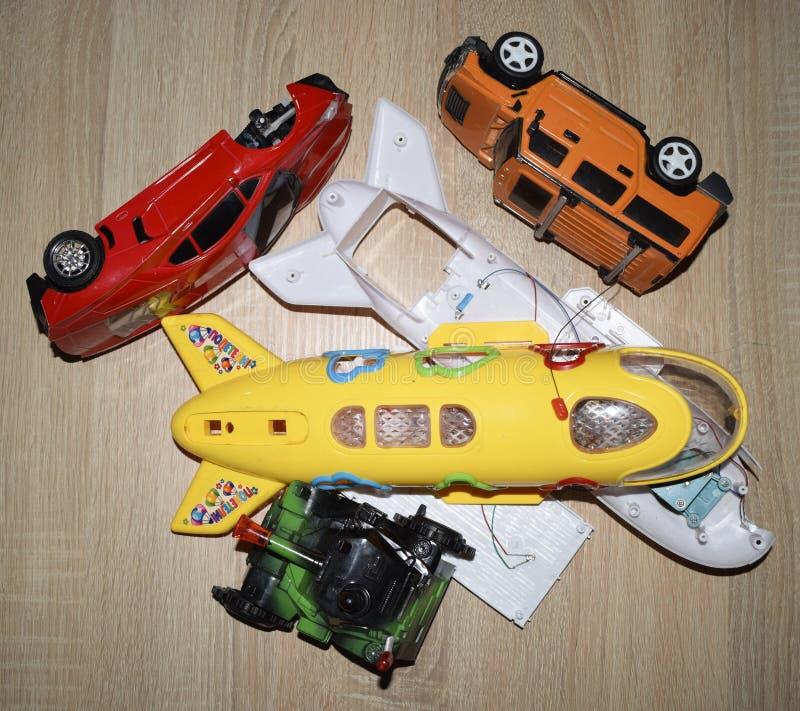 Een ontmantelde stuk speelgoed auto's en vliegtuig dat in verscheidene stukken op houten bureau worden verdeeld royalty-vrije stock fotografie