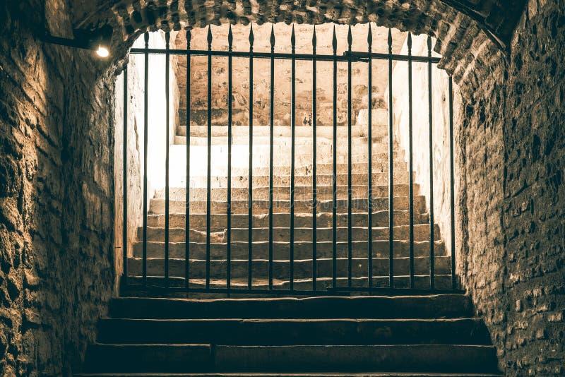 Een ontmoedigende trap die die tot een passage leiden door een ijzernet wordt geblokkeerd in een middeleeuwse kerker stock afbeelding