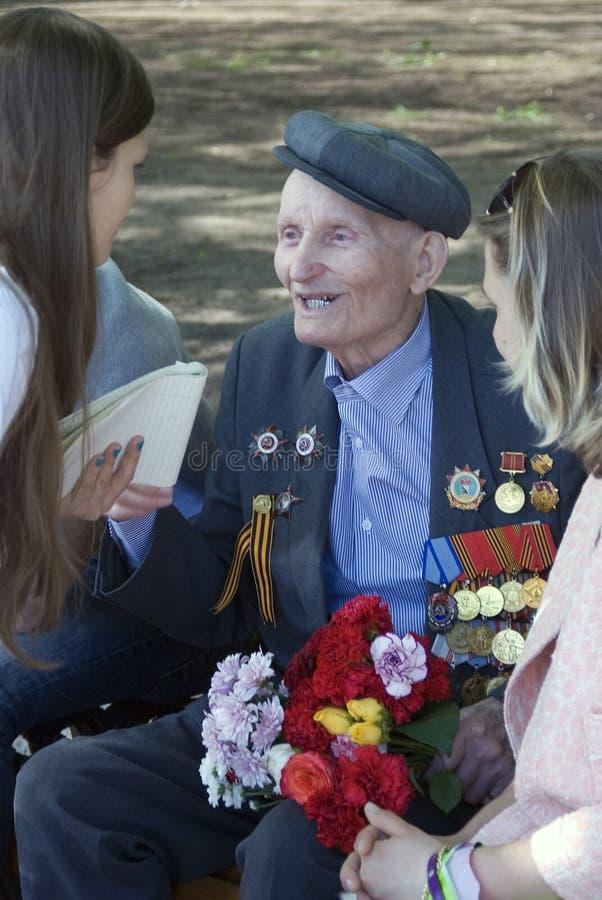 Een oorlogsveteraan spreekt yto jonge vrouwen en glimlacht royalty-vrije stock afbeelding