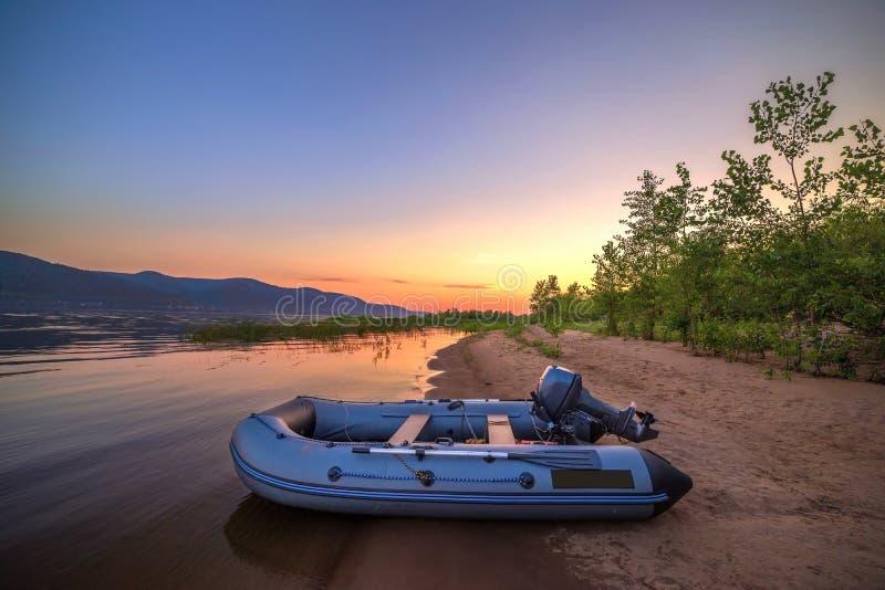 Een opblaasbare boot met een motor op de kust van een zandig strand tegen de achtergrond royalty-vrije stock foto