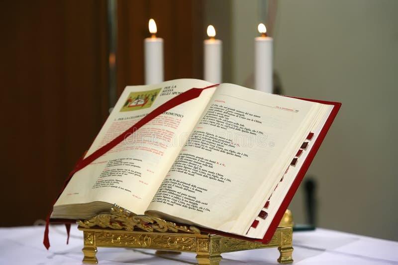 Een open Bijbel en drie kaarsen achter het stock foto