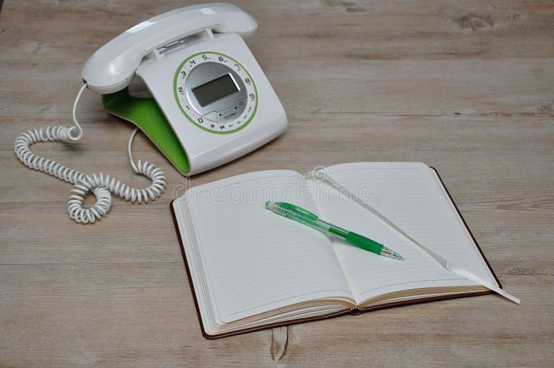 Een open boek met een potlood en uit nadruktelefoon royalty-vrije stock fotografie