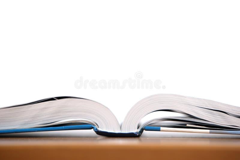 Een open boek op een bureau stock foto's