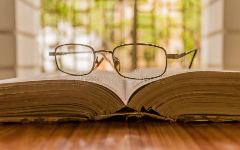 Een open boek op lijst en bril of oogglas op houten lijst, op een warme zonnige ochtend, zijaanzicht dichte omhooggaand Het Conce stock foto's