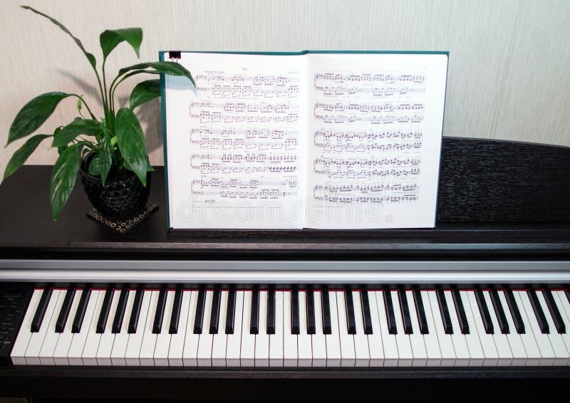Een open boek van bladmuziek op de piano Een samenstelling van de bladmuziek, bloem en het pianotoetsenbord stock fotografie