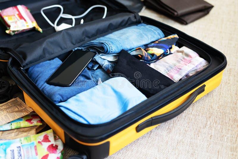 Een open die koffer met de kleding van mensen, voor een zakenreis wordt ingepakt stock foto