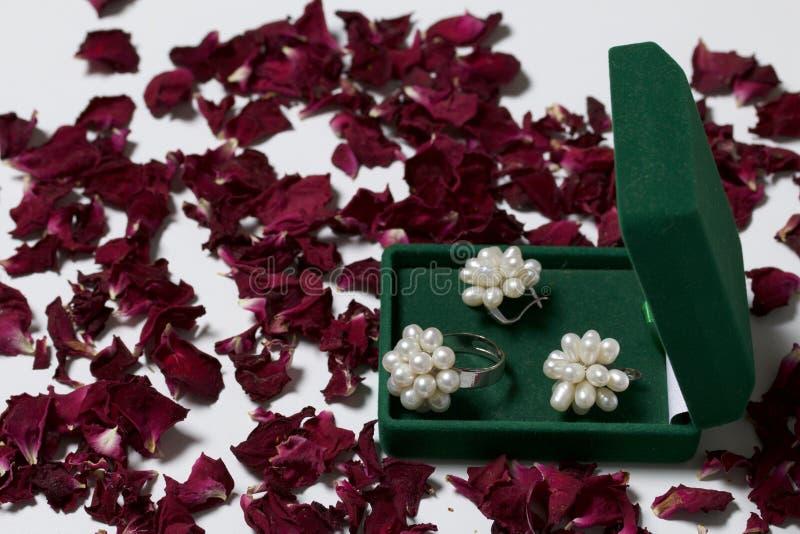 Een open groene fluweeldoos voor juwelen Daarin ligt een reeks: een ring en oorringen met parels Voor een witte die achtergrond,  royalty-vrije stock afbeeldingen