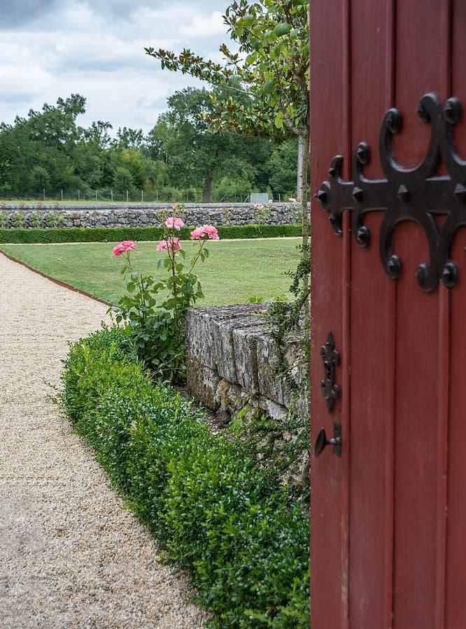 Een open poort nodigt u aan de tuin met rozen uit stock afbeelding