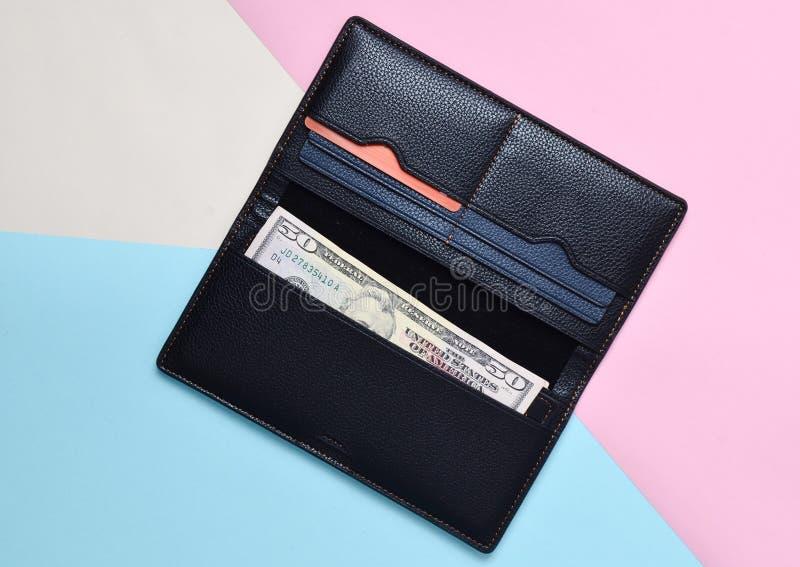 Een open zwarte beurs met dolar rekeningen en creditcards op een multicolored pastelkleurachtergrond Tendens van minimalism stock fotografie