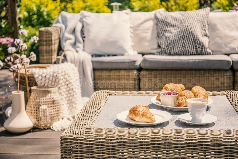 Een openlucht rieten lijst en een bank met kussens Croissants voor royalty-vrije stock afbeeldingen