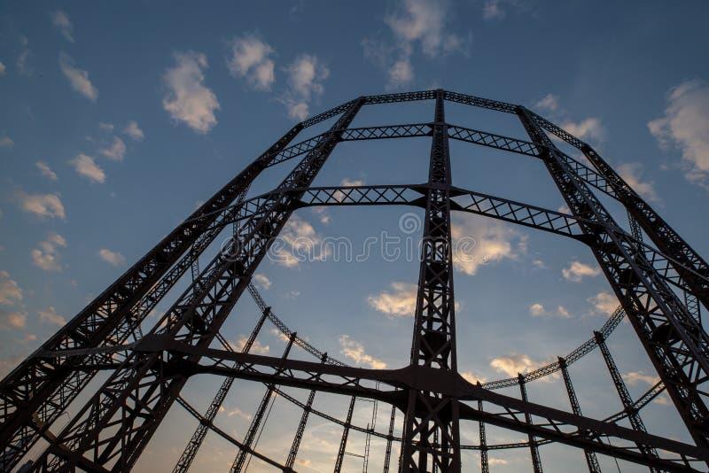 Een opvallend silhouet van een lege cilinder van de gasopslag tegen de schemerhemel in Oost-Londen stock foto
