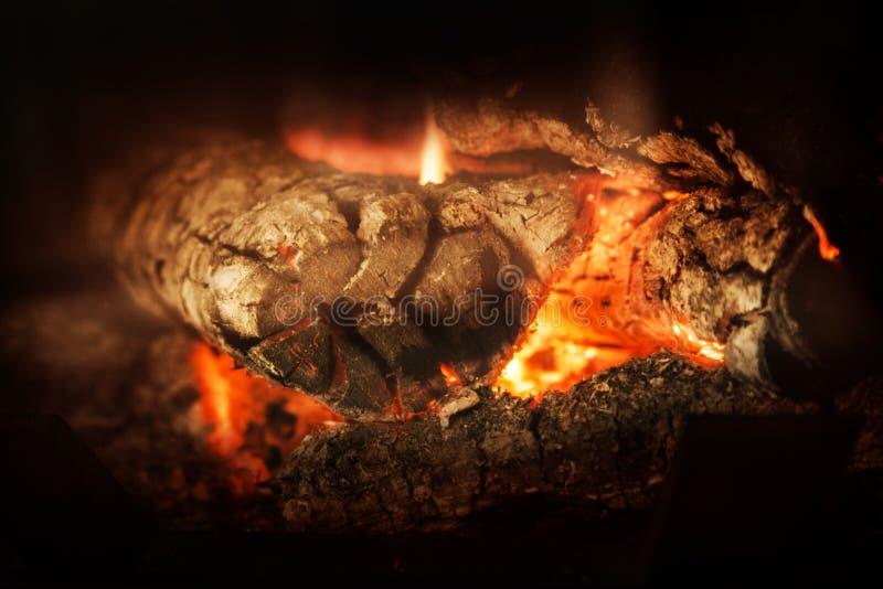 Een opvlammende houten brand in open haard stock foto's
