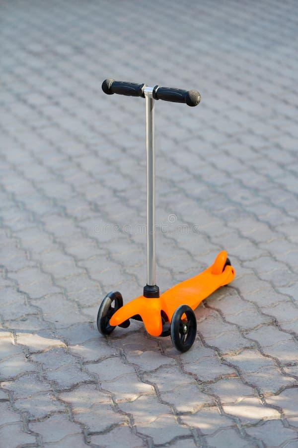 Een oranje kinderen` s autoped bevindt zich op de weg De zomer, rust, sport stock foto's