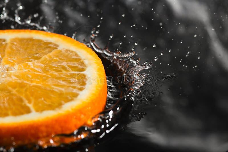 Een oranje ring met plonsen van water, een fruit met plonsen stock foto's