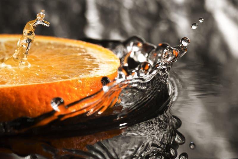 Een oranje ring met plonsen van water, een fruit met plonsen royalty-vrije stock afbeelding