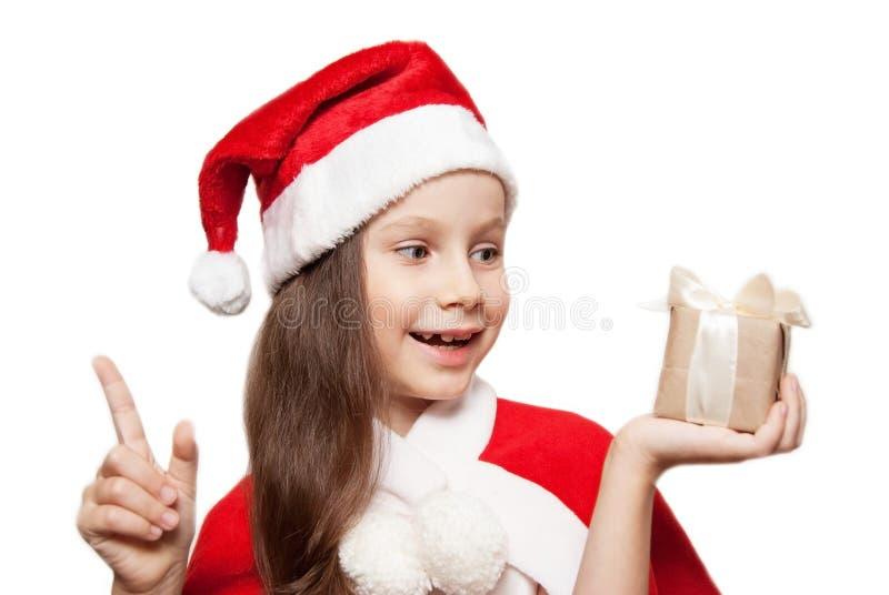 Een 7 oren oud Meisje met Kerstmisgift thinkig van Welke Santa Bring aan haar stock foto