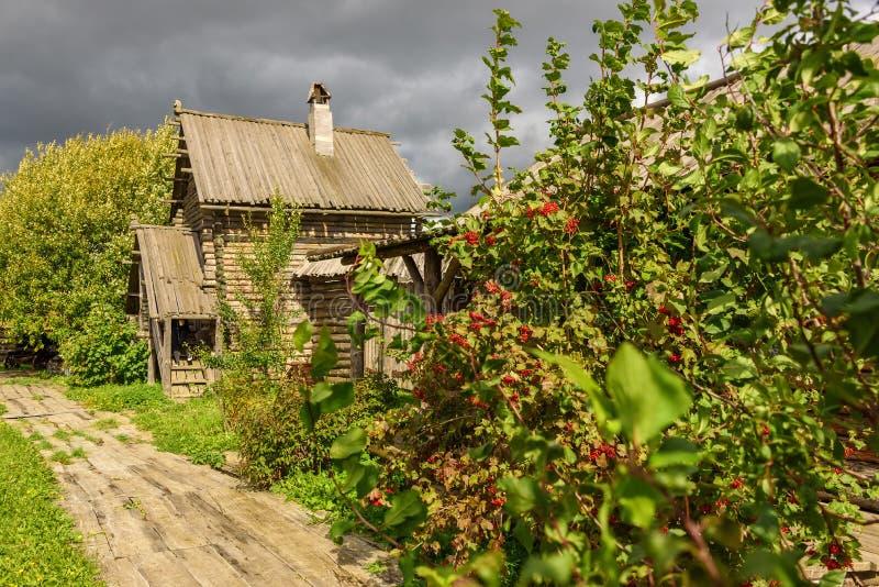 Een oud blokhuis en een weg aan het in de zomer in bewolkt weer royalty-vrije stock fotografie