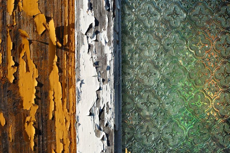 Een oud blokhuisvenster met het pealing van verf en oud verfraaid vensterglas stock foto's