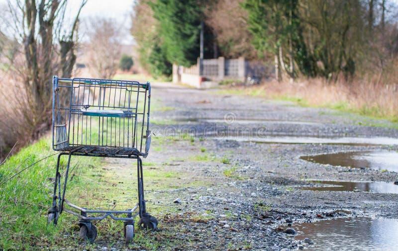 Een oud boodschappenwagentje/een karretje zitten op een grintweg stock fotografie