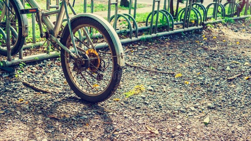Een oud fietsparkeren in de post van het fietspark met een retro vint stock afbeelding