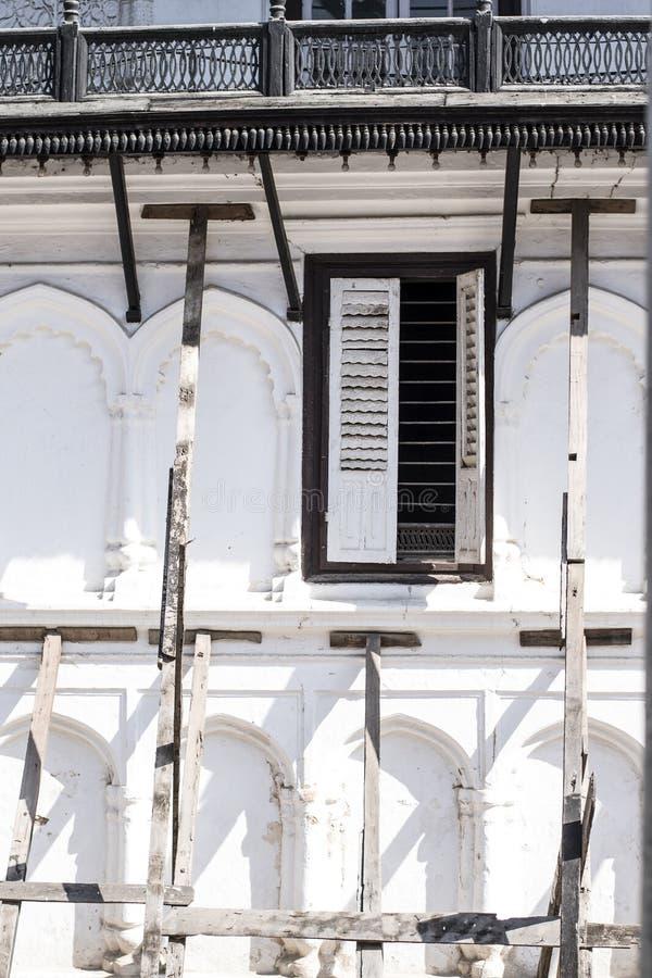 Een oud gebouw dat door houten pijlers wordt gesteund en gedeeltelijk open venster stock foto