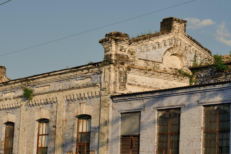 Een oud gebouw met vensters, op het dak waarvan de bomen en het gras groeien stock afbeelding