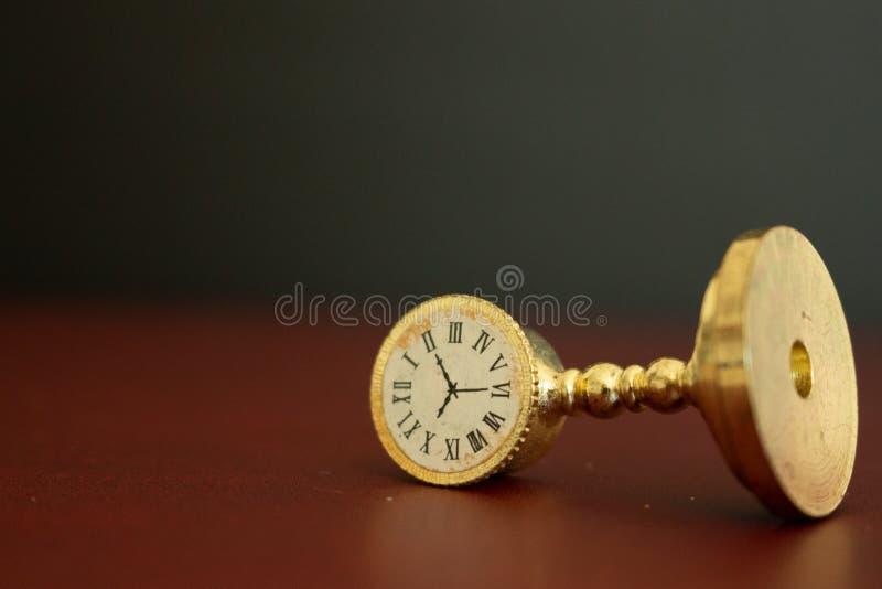 Een oud gouden klok of een horloge die de tijd tonen die uit lopen stock afbeeldingen